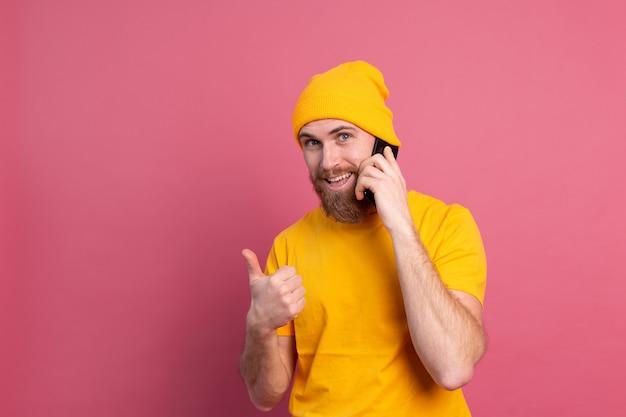 Europese knappe gelukkig vrolijke man praten over smartphone lachend op roze