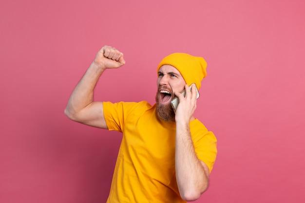 Europese knappe man praten over smartphone schreeuwen trots en vieren overwinning en succes erg opgewonden op roze