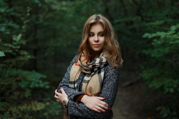 Europese lieve jonge vrouw met blond haar in een luxe grijze jas met een geruite vintage sjaal poseren in een park in de buurt van de groene bomen