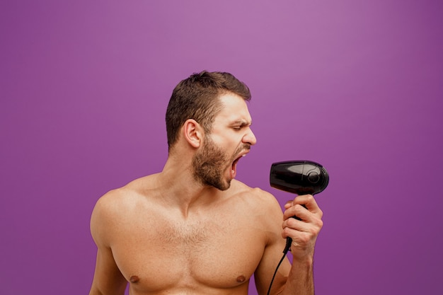 Europese man houdt en zingt in haardroger. profiel van:: knappe jonge bebaarde man met open mond. geïsoleerd op paarse achtergrond. studio opname. ruimte kopiëren