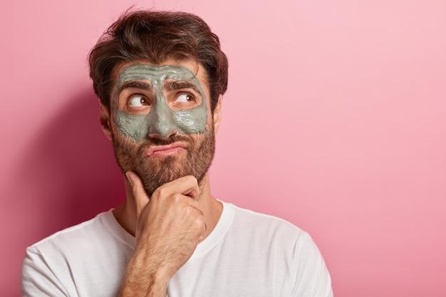 Europese man houdt kin vast, tuit lippen, heeft een bedachtzame uitdrukking, dikke haren, kijkt opzij, past kleimasker op gezicht, draagt een wit t-shirt verfrist de huid, modellen over roze muur. mannelijke cosmetologie