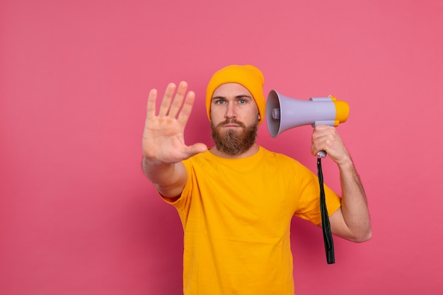 Europese man houdt megafoon stopbord op roze achtergrond weergeven