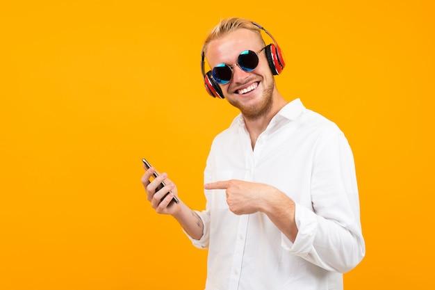 Europese man in een wit overhemd en een zonnebril met een telefoon luistert naar muziek in grote koptelefoon geïsoleerd geel.