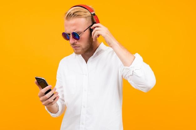 Europese man in een wit overhemd en zonnebril met een telefoon luistert naar muziek in grote koptelefoon op geel.