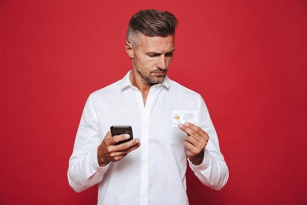 Europese man in wit overhemd met creditcard en smartphone geïsoleerd op rood