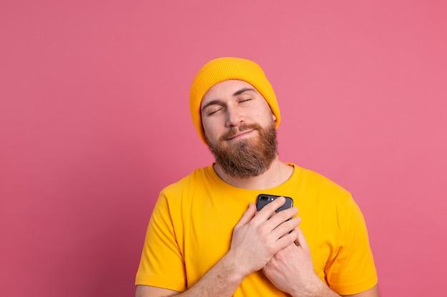 Europese man kreeg een mooie boodschap, met een mobiele telefoon glimlachend op roze