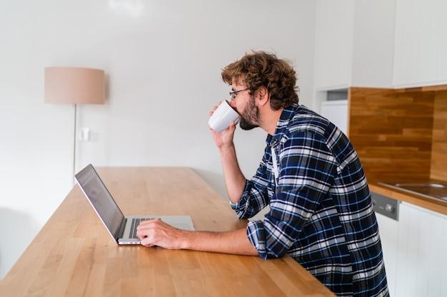 Europese man met baard in geruit overhemd bezig met laptop in de keuken thuis.