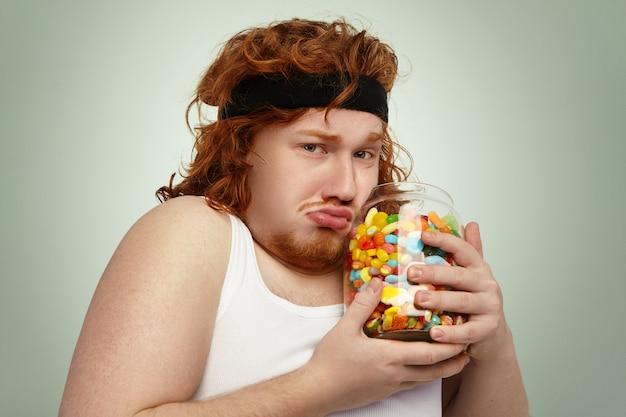 Europese man met overgewicht draagt fitness haarband en tanktop na intensieve cardiotraining, doet zijn best om overgewicht te bestrijden, ziet er ongelukkig uit en houdt een grote pot met verboden snoepjes in zijn handen