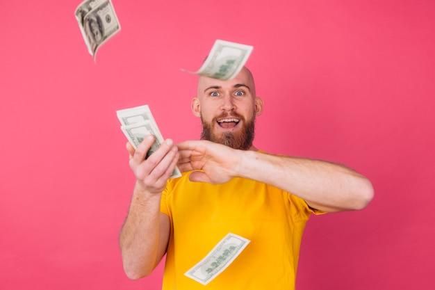 Europese man, met ventilator op 100 dollar blij opgewonden gooien in lucht geïsoleerde ruimte