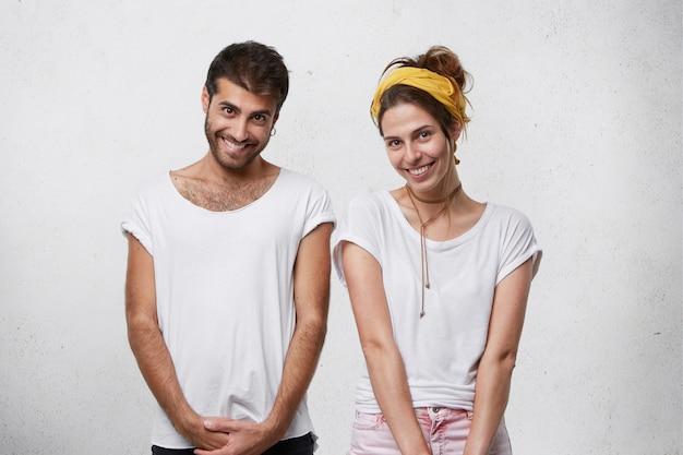 Europese mannelijke en vrouwelijke dragen witte t-shirt glimlachend oprecht met verlegen uitdrukkingen. positieve mensen die hun goed humeur tonen en glimlachen