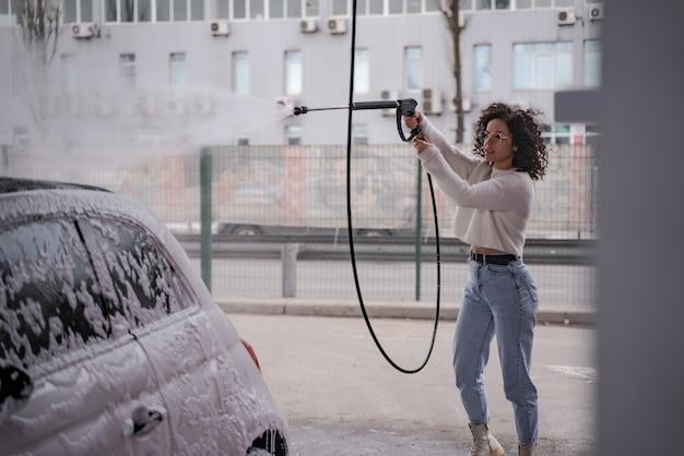 Europese meisje wast persoonlijke auto op self-car wash. jonge krullend geconcentreerde vrouw in glazen auto van slang drenken. auto bedekt met water en zeep