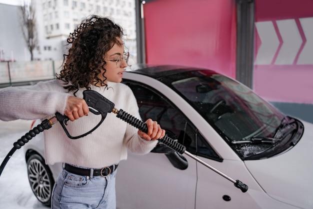 Europese meisjeswas persoonlijke auto op zelfbedieningsautowasserette. jonge gekrulde gerichte vrouw in glazen auto van slang drenken. auto bedekt met water en zeep