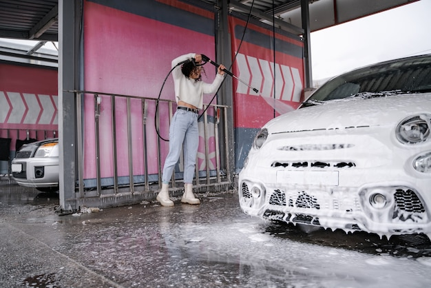 Europese meisjeswas persoonlijke auto op zelfbedieningsautowasserette. jonge krullende lachende vrouw in glazen auto van slang drenken. auto bedekt met water en zeep