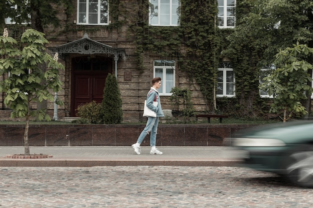 Europese modieuze jongeman in stijlvolle jeanskleding in sneakers met stoffen tas loopt op straat in de buurt van de weg. mode stedelijke man reizen op stad in de buurt van oud gebouw begroeid met bladeren.