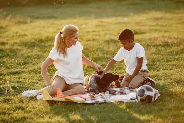 Europese moeder en afrikaanse zoon. familie in een zomerpark. mensen die op de deken zitten.