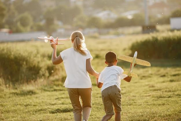 Europese moeder en afrikaanse zoon. familie in een zomerpark. mensen spelen met vliegtuig.