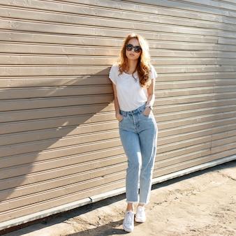 Europese mooie jonge hipster vrouw in stijlvol wit t-shirt in vintage jeans in trendy zonnebril staat in de buurt van de houten muur en geniet van de zomer