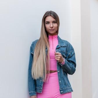 Europese mooie jonge vrouw in trendy roze top in roze korte broek in een denim jasje met blond lang haar ontspant staande in de buurt van een vintage muur in de stad. aantrekkelijk schattig meisje buitenshuis. jeugdstijl.