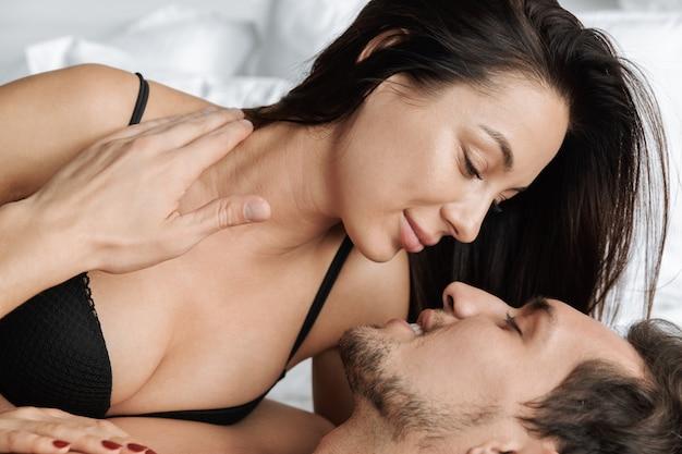 Europese paar man en vrouw samen knuffelen, liggend in bed thuis of hotel appartement