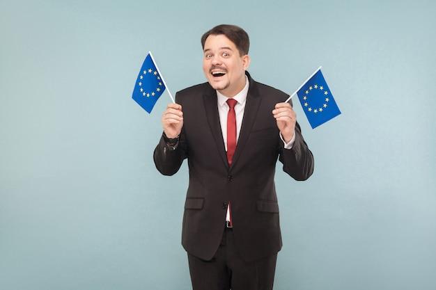 Europese politicus houdt vlaggen vast en glimlacht