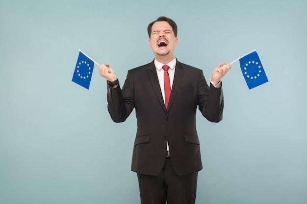 Europese politicus houdt vlaggen vast en verheugt zich. binnen, studio-opname, geïsoleerd op lichtblauwe of grijze achtergrond