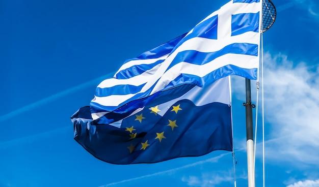 Europese politieke nieuws grexit en natie concept vlaggen van griekenland en europese unie op blauwe hemel achtergrond politiek van europa