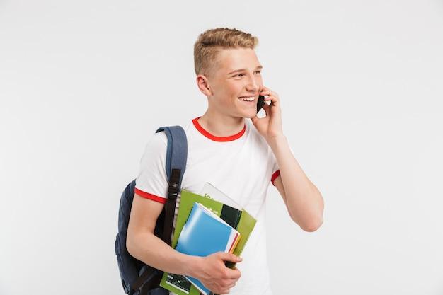 Europese positieve studentenkerel die rugzak draagt die op smartphone met glimlach spreekt terwijl het houden van kleurrijke oefenboeken die op wit worden geïsoleerd