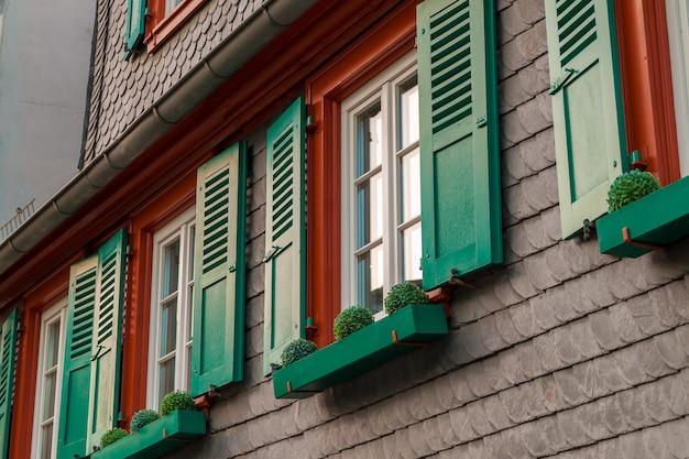 Europese ramen met groene houten luiken in oud huis. buitenshuis buitenshuis