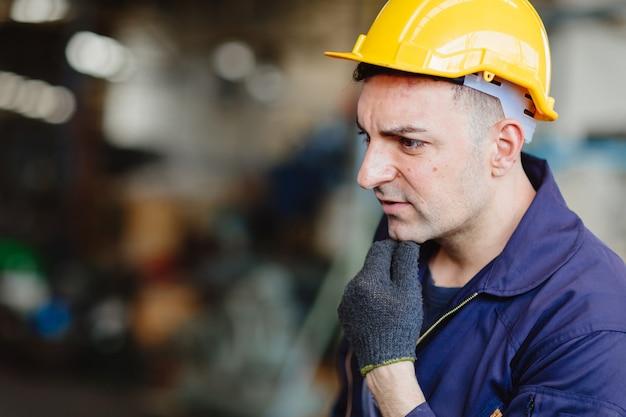 Europese russische arbeider die knappe fabrieksmens denken die het kostuum van de helmveiligheid en handgroef dragen.