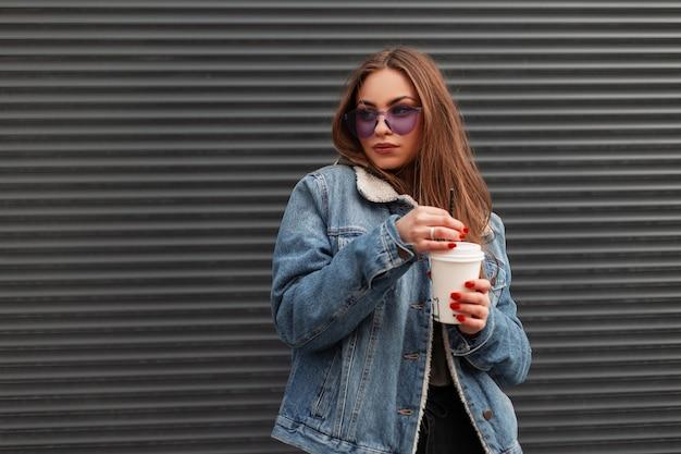 Europese schattige jonge hipster vrouw in modieuze denim blauwe jas in trendy paarse bril met kop warme koffie staat in de buurt van een grijze muur in de stad. vrij mooi meisje poseren op straat.