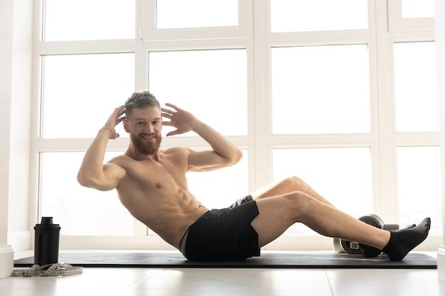Europese sportman doet kraken voor buikspieren op fitnessmat. jonge, bebaarde man met naakte torso. concept van sportactiviteit thuis. interieur van modern ruim appartement. zonnige dag