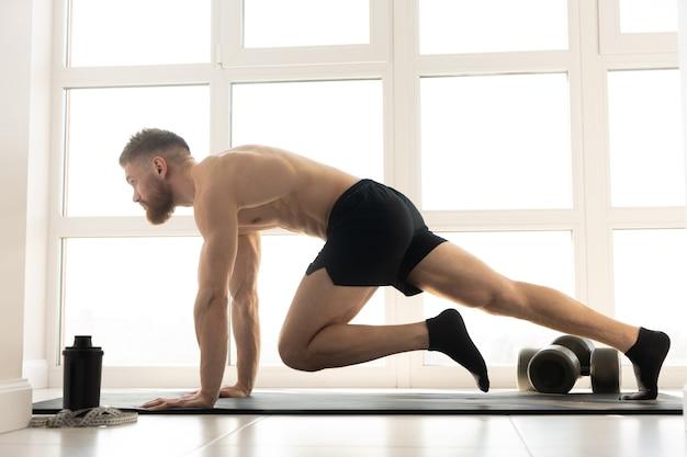 Europese sportman doet oefening voor buikspieren op fitnessmat. jonge, bebaarde man met naakte torso. concept van sportactiviteit thuis. interieur van modern ruim appartement. zonnige dag