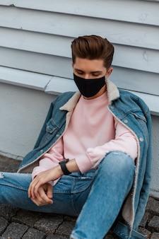 Europese stijlvolle jongeman in denim modieuze blauwe vrijetijdskleding in beschermend zwart masker rust in de buurt van het voortbouwen op straat in de stad. urban fashion model guy is beschermd tegen coronavirus. stijl 2020.