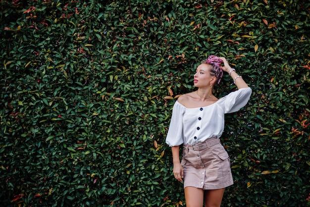 Europese stijlvolle vrouw met roze kleurrijke zomervlechten in beige rok en witte blouse