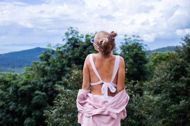 Europese stijlvolle vrouw toeristische staat op de top van de berg met een prachtig tropisch uitzicht op het eiland koh samui thailand mode buiten portret van vrouw