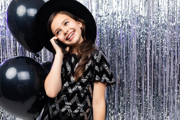 Europese tiener met een telefoon op haar verjaardag op een achtergrond van zwarte helium ballonnen en klatergoud