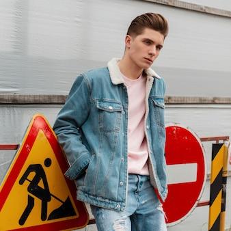 Europese trendy jongeman in stijlvolle blauwe denim kleding in roze vintage t-shirt staat in de buurt van metalen verkeersborden op straat. knappe jongen in casual jeans kleding. casual lente-zomerstijl 2020.