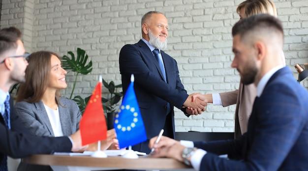 Europese unie en chinese leiders schudden handen op een dealovereenkomst.