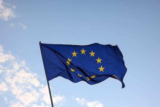 Europese unie eu-vlag vliegen en zwaaien in de wind over heldere blauwe lucht, symbool van europees patriottisme, lage hoek, zijaanzicht
