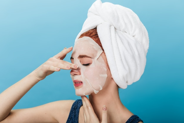 Europese vrouw die met handdoek op hoofd gezichtsmasker toepast. studio shot van geweldig meisje doet kuur op blauwe achtergrond.