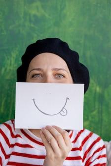 Europese vrouw in een zwarte baret die een sticker vasthoudt met een smiley als een geschilderde glimlach als masker o