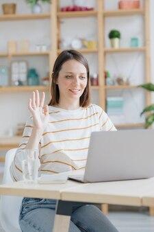 Europese vrouw in haar thuiskantoor werkt met een laptop of kijkt naar een webinar een blanke vrouw