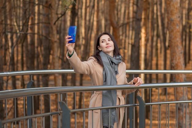 Europese vrouw in jas met telefoon. selfie maken. bij atumn city. hoge kwaliteit foto