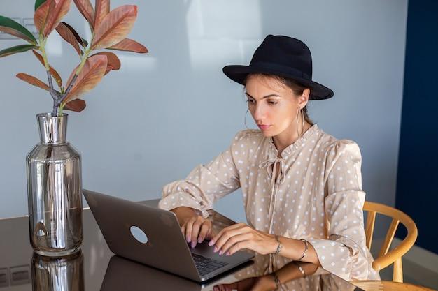 Europese vrouw in jurk en klassieke hoed werkt thuis in de keuken