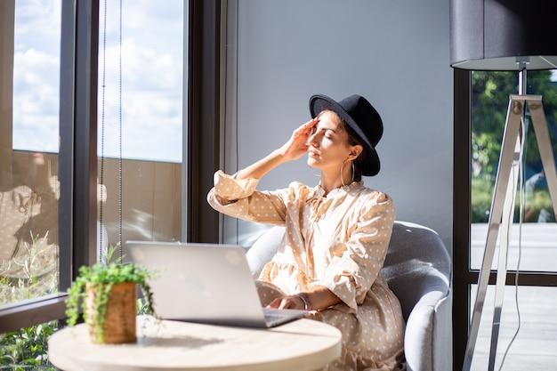 Europese vrouw in jurk en klassieke hoed werkt thuis in de keukenç