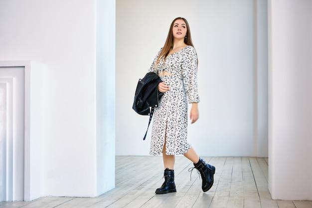 Europese vrouw in militaire stijl laarzen staat in de kamer