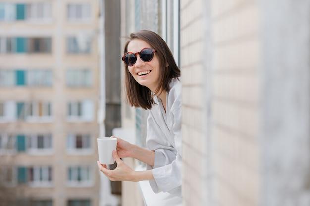 Europese vrouw in zonnebril en met een mok koffie of thee die uit het raam kijkt