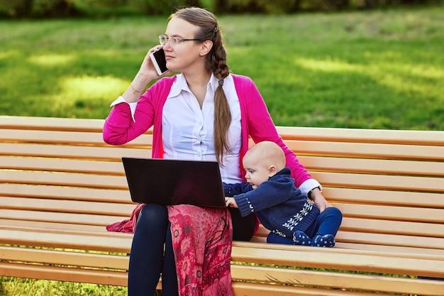 Europese vrouw met baby zit buiten met laptop en praat via smartphone
