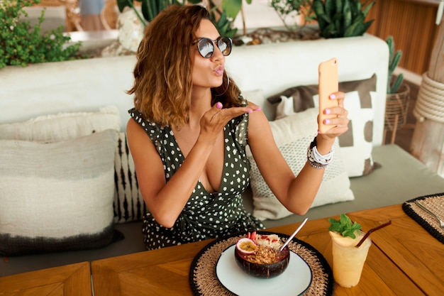 Europese vrouw met behulp van mobiele telefoon in café.
