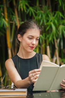 Europese vrouw met een boek op een terras met een tuin